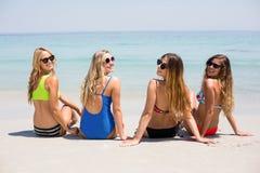 Amis féminins dans le bikini détendant à la plage pendant le jour ensoleillé Images libres de droits