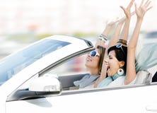 Amis féminins dans le cabriolet avec des mains vers le haut Photos libres de droits