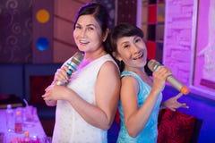 Amis féminins dans le karaoke images stock