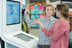 Amis féminins dans le magasin électronique Photographie stock libre de droits