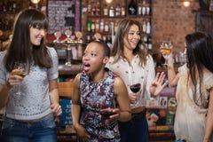 Amis féminins dansant au bar Images stock
