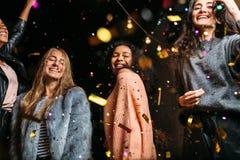Amis féminins dansant sous des confettis la nuit Images libres de droits