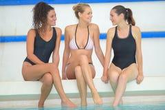 Amis féminins de groupe heureux ayant l'amusement dans la piscine Photos libres de droits
