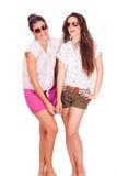 Amis féminins de jeunes couples riant sur le blanc Photos stock