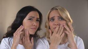 Amis féminins de l'adolescence regardant dans le miroir, notant des boutons sur le visage, peau de problème banque de vidéos