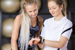 Amis féminins de séance d'entraînement à l'aide du podomètre dans le gymnase Images stock