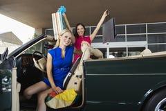 Amis féminins de Shopaholic dans le convertible Images stock