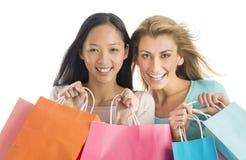 Amis féminins de Shopaholic portant des paniers Image libre de droits