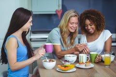 Amis féminins de sourire à l'aide du smartphone Photo stock
