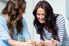 Amis féminins de sourire à l'aide du téléphone portable Photographie stock