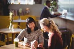 Amis féminins de sourire à l'aide de la tablette au café Photos libres de droits