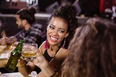 Amis féminins de sourire appréciant la boisson à la table Photo libre de droits