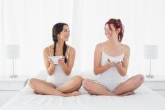 Amis féminins de sourire avec des cuvettes se reposant sur le lit Photos libres de droits