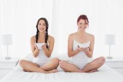 Amis féminins de sourire avec des cuvettes se reposant sur le lit Photos stock