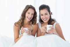 Amis féminins de sourire avec des tasses de café dans le lit Image libre de droits