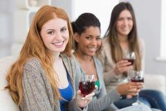 Amis féminins de sourire avec des verres de vin à la maison Photographie stock
