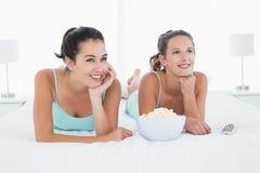 Amis féminins de sourire avec le bol de maïs éclaté se situant dans le lit Photographie stock libre de droits