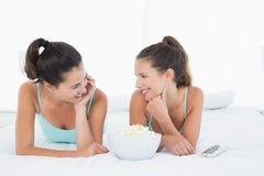 Amis féminins de sourire avec le bol de maïs éclaté se situant dans le lit Images libres de droits