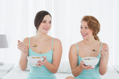 Amis féminins de sourire avec saladier se reposant sur le lit Photos libres de droits