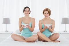 Amis féminins de sourire avec saladier se reposant sur le lit Photo libre de droits