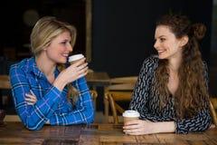 Amis féminins de sourire ayant le café tout en parlant en café Photos stock