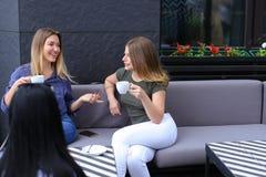 Amis féminins de sourire buvant du café et s'asseyant au café Photos stock