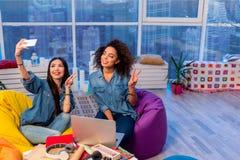 Amis féminins de sourire créant le selfie Image stock