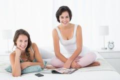 Amis féminins de sourire décontractés avec la magazine dans le lit Photos stock