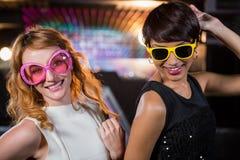 Amis féminins de sourire dansant sur la piste de danse Photo stock