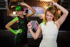 Amis féminins de sourire dansant sur la piste de danse Photos libres de droits