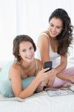 Amis féminins de sourire lisant le message textuel dans le lit Image libre de droits