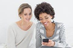 Amis féminins de sourire lisant le message textuel sur le lit Photographie stock libre de droits