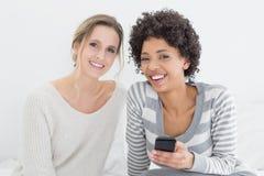 Amis féminins de sourire lisant le message textuel sur le lit Images stock