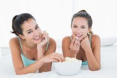 Amis féminins de sourire mangeant du maïs éclaté dans le lit Images stock