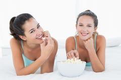 Amis féminins de sourire mangeant du maïs éclaté dans le lit Photo libre de droits