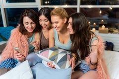 Amis féminins de sourire observant au mobile Image stock
