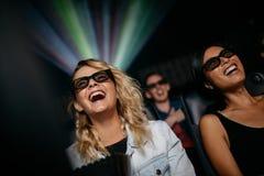 Amis féminins de sourire observant le film 3d Image libre de droits