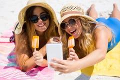 Amis féminins de sourire parlant le selfie tout en ayant des glaces à l'eau Image libre de droits