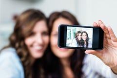 Amis féminins de sourire photographiant avec le smartphone Images stock