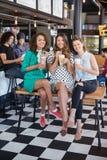 Amis féminins de sourire posant avec des smoothies au restaurant Image stock
