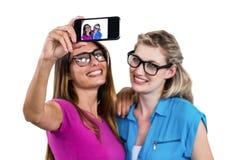 Amis féminins de sourire prenant l'autoportrait Photos libres de droits
