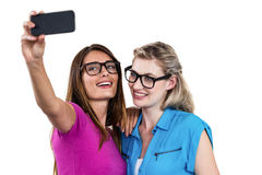 Amis féminins de sourire prenant l'autoportrait avec le smartphone Photo stock