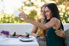 Amis féminins de sourire prenant le selfie au restaurant Image stock