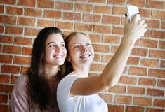 Amis féminins de sourire prenant un selfie Images libres de droits