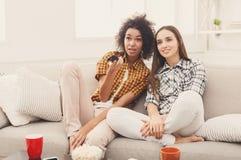 Amis féminins de sourire regardant la TV à la maison Photos stock
