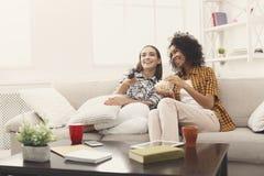 Amis féminins de sourire regardant la TV à la maison Photos libres de droits
