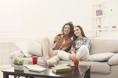 Amis féminins de sourire regardant la TV à la maison Photo stock