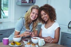 Amis féminins de sourire s'asseyant à la table de petit déjeuner Photographie stock libre de droits