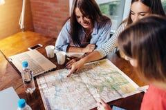Amis féminins de sourire s'asseyant au bureau prévoyant leurs vacances recherchant des destinations sur la carte Photos stock
