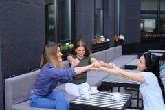 Amis féminins de sourire s'asseyant au café et à tenir des mains Images libres de droits